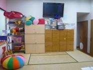 畳スペースとテレビ、DVDプレーヤーです。おやつを食べたり、みんなでテレビを観たり、クッションでゴロゴロする場になっています。また、子ども達の着替え、スタッフの荷物、おもちゃの保管スペースでもあります。